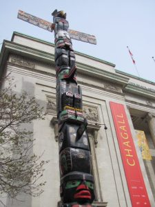 'Healing Reconciliation,' carved by artist Charles Joseph from Kwakwaka'wakw Nation, BC, being raised outside the Montreal Museum of Fine Arts.
